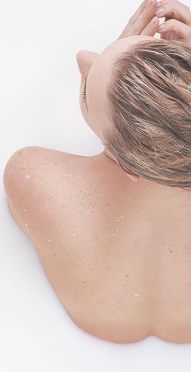 Cuerpo de una mujer de espaldas hidratándose en un baño de leche corporal